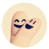 Two crossed fingers with happy faces drawn on.
